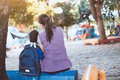 亚裔母亲和女儿有一起坐的背包的 免版税库存照片