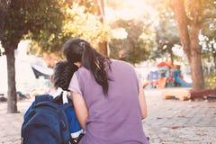 亚裔母亲和女儿有一起坐的背包的 库存图片
