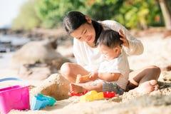 亚裔母亲和婴孩演奏沙子和玩具togather 免版税库存图片