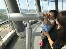 亚裔母亲和逗人喜爱的婴孩喜欢看双筒望远镜 免版税图库摄影