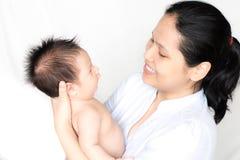 亚裔母亲抱着她新出生的婴孩 库存照片