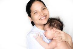 亚裔母亲抱着她新出生的婴孩 免版税库存照片
