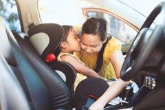 亚裔母亲紧固安全传送带给她的汽车的女儿 库存照片