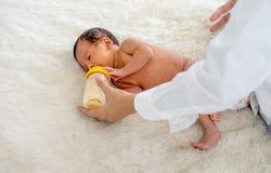 亚裔母亲给哺养与瓶的牛奶在白色床上的一点新生儿并且保重 图库摄影