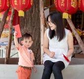 亚裔母亲给一个红色信封或Ang战俘儿子 免版税库存照片