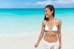 亚裔比基尼泳装妇女放松的走在白色海滩 库存图片