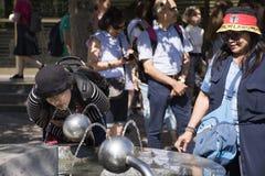 亚裔泰国从公开饮用水的妇女饮用水在庭院正方形 免版税库存图片