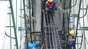 亚裔泰国在建造场所的工作者和大量手段运作的建造者新的大厦 股票视频