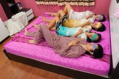 亚裔泰国女孩和男孩与转动的面孔u睡觉 免版税库存照片