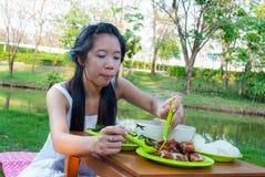 亚裔泰国女孩在沼泽旁边吃着 免版税库存照片