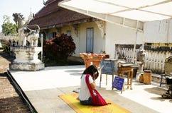 亚裔泰国妇女人民尊敬祈祷的菩萨雕象和chedi 库存图片