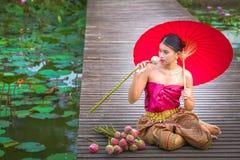 亚裔泰国妇女坐在莲花的一个木平台 库存图片