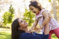 亚裔混合的族种使用在公园的妈咪和年轻女儿 免版税库存图片