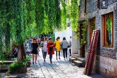 亚裔游人在绿色舒适街道上走在丽江 免版税库存图片