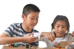 亚裔演奏在白色的男孩和女孩lego 免版税库存照片