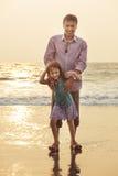 亚裔父亲使用和有与他的海滩的女儿 图库摄影