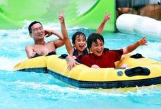 亚裔父亲和儿子有乐趣管材在waterpark 免版税图库摄影