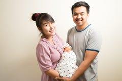 亚裔父母和六个月画象女婴在家 免版税库存图片