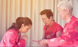 亚裔父母给红色包围给女儿农历新年 免版税图库摄影