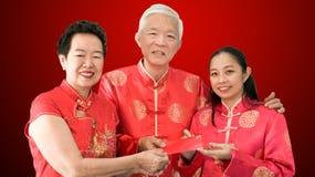 亚裔父母给红色包围给女儿农历新年 库存照片