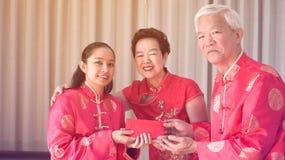 亚裔父母给红色包围给女儿农历新年 免版税库存照片
