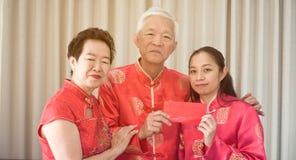 亚裔父母给红色包围给女儿农历新年 图库摄影
