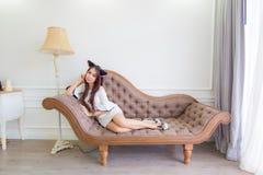 年轻亚裔猫妇女在一个长沙发说谎在现代屋子里 免版税库存图片