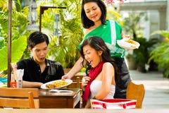亚裔男人和妇女在餐馆 免版税库存照片