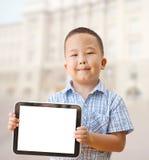 亚裔男孩与片剂的6年 库存照片