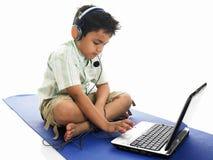 亚裔男孩他膝上型计算机键入 免版税库存照片