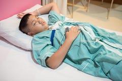 亚裔男孩佩带的睡眠停吸诊断医疗设备成套工具 免版税库存图片