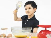 亚裔男孩做蛋糕 免版税库存照片