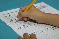 亚裔男孩写与黄色铅笔的信A 库存照片