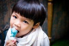 亚裔男孩吃着糖果 免版税库存照片