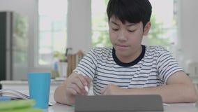 亚裔男孩在家坐一把椅子家庭作业的使用片剂发现答复 影视素材