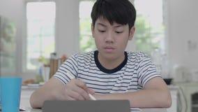 亚裔男孩在家坐一把椅子家庭作业的使用片剂发现答复 股票录像
