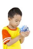 亚裔男孩在他的手上的拿着我们的行星地球。 库存照片