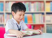 亚裔男孩学生在学校图书馆里 图库摄影