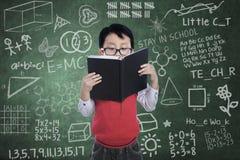 亚裔男孩学生读了在类的书 库存照片