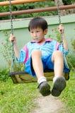 亚裔男孩室外使用的摇摆 免版税库存图片