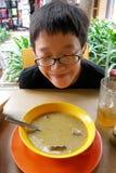 亚裔男孩尝试的街道食物 库存图片