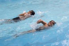 亚裔男孩爬泳在游泳池游泳 免版税库存图片