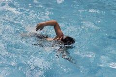 亚裔男孩爬泳在游泳池游泳 库存照片