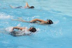 亚裔男孩爬泳在游泳池游泳 免版税库存照片