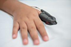 亚裔男孩的手医院佩带的睡眠停吸诊断医疗设备成套工具的 库存图片