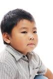 亚裔男孩看起来严重 免版税库存照片