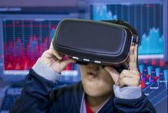 亚裔男孩,在他的头的佩带的虚拟现实玻璃,被激发关于什么他看见 免版税图库摄影