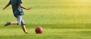亚裔男孩,推力脚准备踢足球作为strengt 免版税库存图片