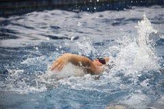 亚裔男孩仰泳在游泳池游泳 库存图片