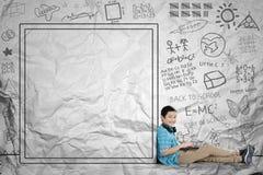 亚裔男小学生在拉长的whiteboard附近坐 免版税图库摄影
